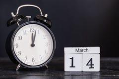 Calendario de madera de la forma del cubo para el 14 de marzo con el reloj negro Imágenes de archivo libres de regalías