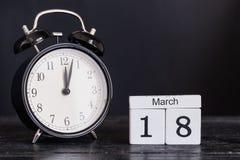 Calendario de madera de la forma del cubo para el 18 de marzo con el reloj negro Foto de archivo libre de regalías