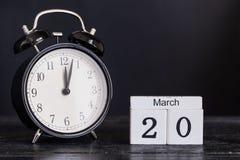 Calendario de madera de la forma del cubo para el 20 de marzo con el reloj negro Foto de archivo libre de regalías
