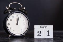 Calendario de madera de la forma del cubo para el 21 de marzo con el reloj negro Foto de archivo libre de regalías