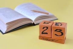 Calendario de madera perpetuo con la fecha del 23 de febrero, de un libro abierto y de un lápiz en un fondo amarillo con el espac imagenes de archivo
