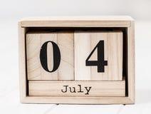 Calendario de madera que muestra el cuarto de julio Fotografía de archivo libre de regalías