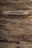 Calendario del cubo para enero y febrero en fondo de madera Foto de archivo