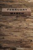 Calendario del cubo para febrero y marzo en fondo de madera Foto de archivo libre de regalías