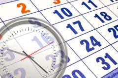 Calendario del calendario de pared con el número de días y de ascendente cercano del reloj Foto de archivo
