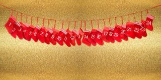 Calendario 1-24 di arrivo Parte posteriore dorata della decorazione rossa di natale Immagine Stock