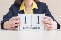 Calendario di legno bianco del primo piano con la parola nera dell'11 dicembre in mano vaga della donna lavoratrice sullo scritto Fotografia Stock Libera da Diritti