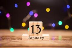 Calendario di legno dei cubi con la data del 13 gennaio Calendario di concetto per l'anno con lo spazio della copia su fondo scur immagine stock libera da diritti