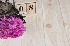 Calendario di legno dell'8 marzo, accanto ai fiori porpora sulla tavola di legno Fotografia Stock Libera da Diritti