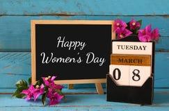Calendario di legno dell'8 marzo, accanto ai fiori porpora sulla vecchia tavola rustica blu Fuoco selettivo Annata filtrata Fotografia Stock