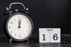 Calendario di legno di forma del cubo per il 16 aprile con l'orologio nero Fotografia Stock Libera da Diritti