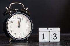 Calendario di legno di forma del cubo per il 13 aprile con l'orologio nero Immagine Stock