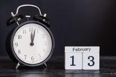 Calendario di legno di forma del cubo per il 13 febbraio con l'orologio nero Immagini Stock Libere da Diritti