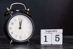 Calendario di legno di forma del cubo per il 15 febbraio con l'orologio nero Immagini Stock Libere da Diritti