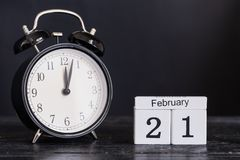 Calendario di legno di forma del cubo per il 21 febbraio con l'orologio nero Immagini Stock Libere da Diritti