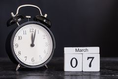 Calendario di legno di forma del cubo per il 7 marzo con l'orologio nero Fotografia Stock Libera da Diritti