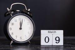 Calendario di legno di forma del cubo per il 9 marzo con l'orologio nero Immagini Stock Libere da Diritti
