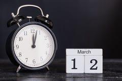 Calendario di legno di forma del cubo per il 12 marzo con l'orologio nero Immagini Stock Libere da Diritti