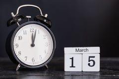 Calendario di legno di forma del cubo per il 15 marzo con l'orologio nero Fotografia Stock Libera da Diritti