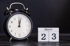 Calendario di legno di forma del cubo per il 23 marzo con l'orologio nero Fotografia Stock