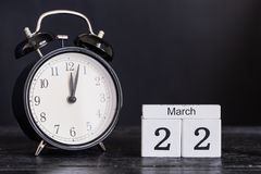 Calendario di legno di forma del cubo per il 22 marzo con l'orologio nero Immagini Stock Libere da Diritti