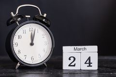 Calendario di legno di forma del cubo per il 24 marzo con l'orologio nero Fotografie Stock