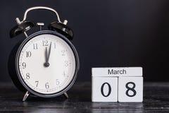 Calendario di legno di forma del cubo per l'8 marzo con l'orologio nero Immagini Stock Libere da Diritti