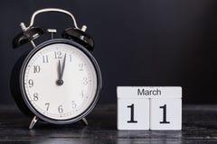 Calendario di legno di forma del cubo per l'11 marzo con l'orologio nero Fotografie Stock