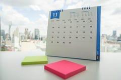Calendario di novembre con il Post-it nel rosa e nel giallo immagine stock libera da diritti
