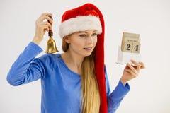 Calendario e campana della tenuta della donna di Natale Fotografia Stock