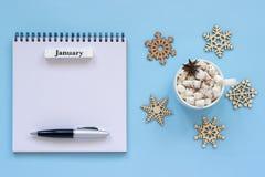 Calendario enero y taza de cacao con la melcocha, libreta abierta vacía imagen de archivo libre de regalías