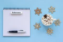 Calendario febrero y taza de cacao con la melcocha, libreta abierta vacía imagen de archivo libre de regalías