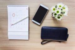 Calendario marcado en el 1r del mes con la cartera y teléfono elegante o m Fotos de archivo libres de regalías