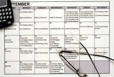 Calendario ocupado, PDA y vidrios Foto de archivo libre de regalías