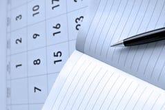 Calendario, página en blanco del cuaderno y pluma negra imagenes de archivo