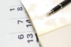Calendario, página en blanco del cuaderno y pluma negra foto de archivo libre de regalías