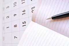 Calendario, página en blanco del cuaderno y pluma negra imagen de archivo libre de regalías