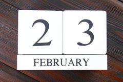 Calendario perpetuo de madera blanco con la fecha del 23 de febrero encendido Foto de archivo libre de regalías
