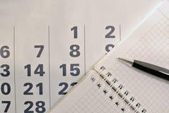 Calendario, pluma y cuaderno con las páginas en blanco imagenes de archivo