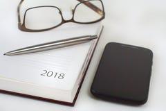 Calendario 2018, smartphone del organizador de la oficina del Año Nuevo, vidrios y Imagen de archivo libre de regalías