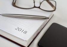 Calendario 2018, smartphone del organizador de la oficina del Año Nuevo, vidrios y Fotografía de archivo