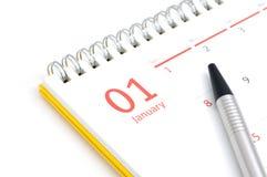 Calendario y pluma de escritorio en el fondo blanco Imágenes de archivo libres de regalías