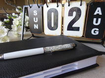 Planning concept: Old metal calendar with leather agenda, stylus and white flowers. Old metal calendar with day, month and number Stock Photo