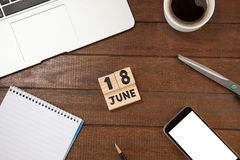 Calender date with coffee cup and book by mobile phone on table. Overhead view of calender date with coffee cup and book by mobile phone on wooden table Stock Photos
