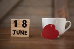 Calender date by coffee cup with heart shape on table. Close up of calender date by coffee cup with heart shape on wooden table Royalty Free Stock Image