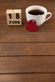 Calender date and coffee cup with heart shape on table. High angle view of calender date and coffee cup with heart shape on wooden table Royalty Free Stock Images