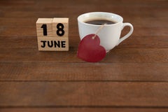 Calender date by coffee cup with heart shape on wooden table. High angle view of calender date by coffee cup with heart shape on wooden table Royalty Free Stock Image