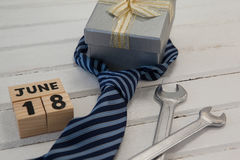 Calender date and gifts for fathers day on table. High angle view of calender date and gifts for fathers day on wooden table Royalty Free Stock Image