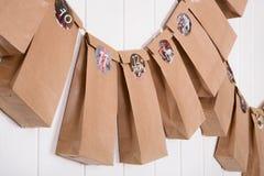 Calendrier bricolé fait main d'avènement avec des sacs en papier et des autocollants Photographie stock libre de droits