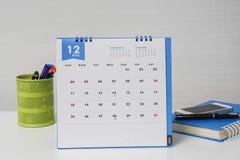 Calendrier de décembre avec la boîte et le carnet stationnaires sur le bureau de femme d'affaires Photo stock